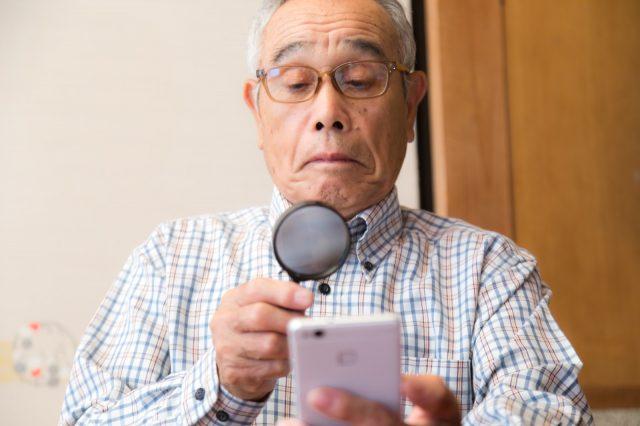 スマホ画面が見えなくて、虫眼鏡で見ているおじいちゃん